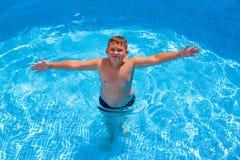 Junge, wenn Spaß im Swimmingpool gehabt wird lizenzfreies stockbild