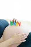 Junge werdende Mutter mit Buchstaben blockiert Rechtschreibungsbaby auf ihrem Bauch Stockfotografie