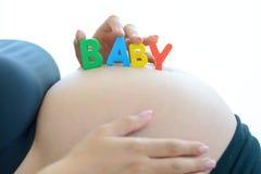 Junge werdende Mutter mit Buchstaben blockiert Rechtschreibungsbaby auf ihrem schwangeren Bauch Stockfoto