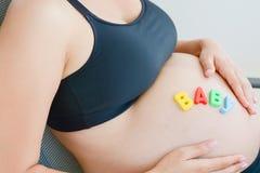 Junge werdende Mutter mit Buchstaben blockiert Rechtschreibungsbaby auf ihrem schwangeren Bauch Lizenzfreies Stockfoto
