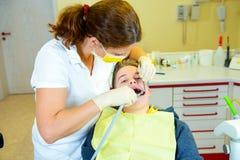 Junge wird herein vom weiblichen Zahnarzt behandelt stockbilder