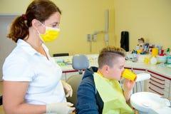Junge wird herein vom weiblichen Zahnarzt behandelt lizenzfreie stockfotos