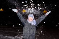 Junge wirft oben ein Arm voll Schnee Lizenzfreie Stockbilder