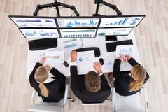 Junge Wirtschaftler, die mit Diagrammen auf mehrfachen Computern arbeiten Lizenzfreie Stockfotografie