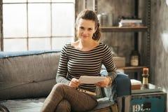 Junge wohlhabende Brünettefrau, die auf Couch sitzt und Tablette hält stockbilder