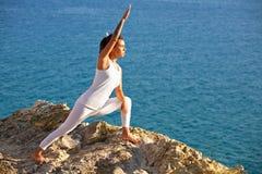 Junge Yogafrau der Meditation, die am Seestrand sich entspannt in der Yogahaltung meditiert Stockbild