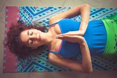 Junge Yogafrau, die auf Matte mit den Händen in namaste Geste abov liegt Stockfotografie