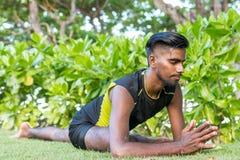 Junge Yogamannpraktiker, die Yoga auf Natur tun Asiatischer indischer Yogismann auf dem Gras im Park Bali-Insel Lizenzfreies Stockbild