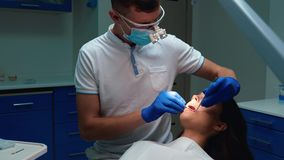 Junge Zahnärzte, die medizinische Handschuhe, Masken und Brillen tragen, versiegeln die Zähne der Patientin mit Zahnspiegel und M stock footage