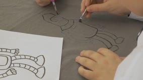 Junge zeichnet einen Roboter auf Papier stock footage