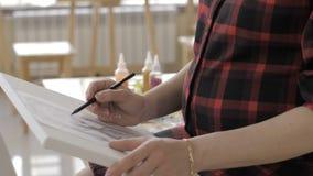 Junge Zeichnungsmalerei der schwangeren Frau im Kunststudio, gesundes gl?ckliches Lebensstilkonzept stock footage