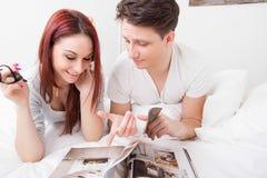 Junge Zeitschrift des glücklichen Paars Lesezusammen im Bett lizenzfreies stockfoto