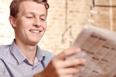 Junge Zeitung des gutaussehenden Mannes Lese lizenzfreies stockbild