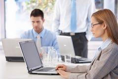 Junge zufällige Büroangestellte, die an Laptop arbeiten stockbild