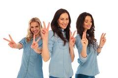3 junge zufällige Frauen, die Siegeszeichen lachen und machen Stockfotos
