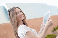 Junge zufällige Geschäftsfrau, die Tablette auf einem Bruch verwendet Stockfotos