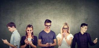 Junge zufällige Leute, die den Handy zusammen steht gegen Betonmauer verwenden lizenzfreies stockbild