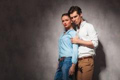 Junge zufällige Paarstellung umfasst im Studio Stockfotografie