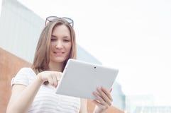 Junge zufällige Geschäftsfrau, die Tablette auf einem Bruch verwendet Lizenzfreies Stockfoto
