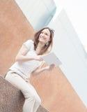 Junge zufällige Geschäftsfrau, die Tablette auf einem Bruch verwendet Lizenzfreies Stockbild