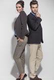 Junge zufällige Paare, die zurück zu Rückseite aufwerfen Stockfoto