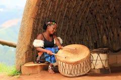 Junge Zulufrau, die Trommeln in Südafrika spielt Stockfoto