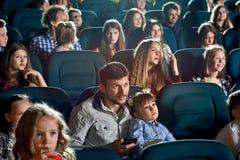 Junge Zuschauer, die Karikatur aufpassen und im Kino lächeln Lizenzfreie Stockfotos