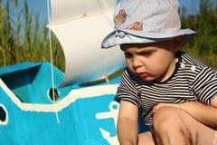 Junge zwei Jahre auf dem Hintergrund eines selbst gemachten Schiffs Lizenzfreie Stockfotos