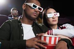 junge zwischen verschiedenen Rassen Paare in den Gläsern 3d mit aufpassendem Film des Popcorns stockfotos