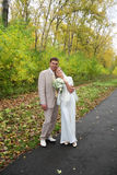 Jungebräutigam umarmt seine Braut im Herbstpark Stockfotografie