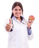 Jungekrankenschwester, die Apfel hält Lizenzfreie Stockfotos
