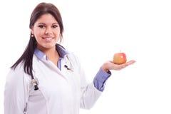 Jungekrankenschwester, die Apfel lokalisiert auf Weiß hält Lizenzfreie Stockfotografie