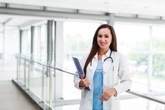 Jungekrankenschwester, die am Arbeitsplatz am Krankenhaus aufwirft Stockfotos