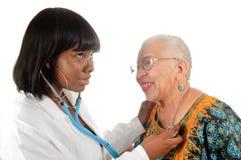 Jungekrankenschwester, die Patienten überprüft stockfotos