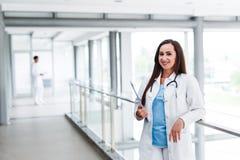 Jungekrankenschwester, die vor ihrem Kollegen aufwirft Stockbilder