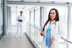 Jungekrankenschwester, die vor ihrem Kollegen aufwirft Stockfoto