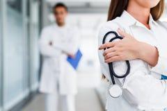 Jungekrankenschwester, die vor ihrem Kollegen aufwirft Stockfotografie