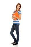 Jungelächelnde Jugendfrau, die Bücher hält stockbilder