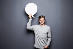 Jungelächelnmann, der weiße leere Spracheblase mit Raum für den Text lokalisiert auf grauem Hintergrund hält Stockbild