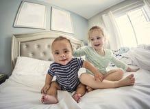 Jungelachen und spielerische Kinder zusammen zu Hause spielend Lizenzfreies Stockbild