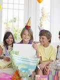 Jungen-Öffnungs-Geschenk mit Gästen an der Partei stockfotografie