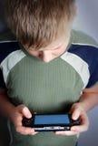 Jungen übergeben das Spielen des beweglichen Videospiels Stockbild