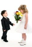 Jungen-überraschendes Mädchen mit Blumen Stockbild