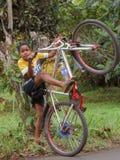 Jungen-anhebendes Fahrrad lizenzfreie stockbilder