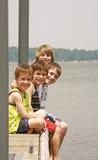 Jungen auf dem Dock lizenzfreie stockbilder