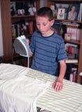 Jungen-bügelnde Kleidung lizenzfreie stockfotografie