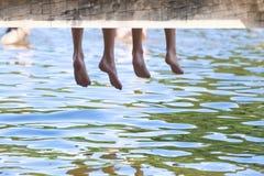 Jungen-Beine, die unten vom hölzernen Pier baumeln lizenzfreie stockbilder
