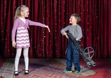 Jungen-Clown Aiming Large Gun am blonden Mädchen Lizenzfreie Stockfotos