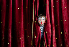 Jungen-Clown-Peering Through Stage-Vorhänge Lizenzfreie Stockfotos