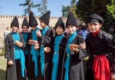 Jungen in den georgischen Kostümen der Weinlese sprechend in einer Menge des Weinfestivals Lizenzfreie Stockfotografie